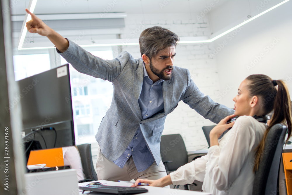 Fototapeta Angry boss firing upset female employee in office. Young male business manager yelling at scared and stressed business woman at her workplace.
