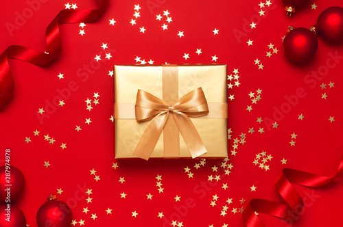 fototapeta na drzwi i meble New Year Christmas golden presents with ribbon, Christmas balls, gold confetti stars on red background top view. Flat lay Xmas holiday 2020 celebration. Gift boxes greeting card Festive decorations