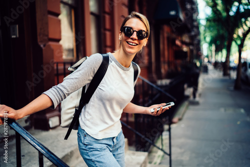 Vászonkép Half length portrait of cheerful young woman leaving building laughing holding t