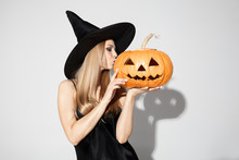 Young Blonde Woman In Black Hat And Costume On White Background. Attractive Caucasian Female Model Posing. Halloween, Black Friday, Sales, Autumn Concept. Copyspace. Kissing A Pumpking.
