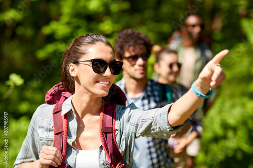 Foto auf Leinwand Texturen travel, tourism, hike and people concept - woman showing something to group of friends walking with backpacks in forest