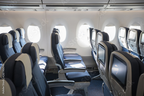 An economy class empty cabin of the airplane - empty blue chairs - monitors on the back of the chairs