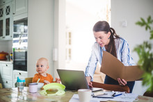 Female Professional Holding File While Using Laptop By Daughter On Dining Table At Home Office