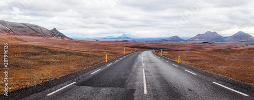 Foto auf AluDibond Dunkelbraun Iceland. Panoramic landscape of Icelandic volcanic nature with asphalt road curved away over horizon. Traveling by Iceland background. Road trip concept.