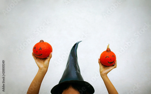 Photo Closeup of happy Halloween witch holding orange pumpkin, isolated on white background