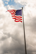 """American Flag Waving Atop A Flagpole Against A Cloudy Darkening Grey Sky Towards Bottom Of Frame And A Patch Of Clear Blue Sky Just Above """"Old Glory""""."""
