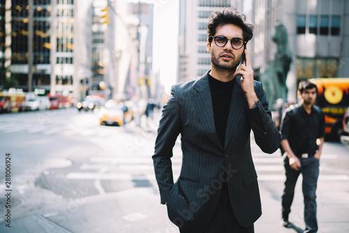 Fototapeta Half length portrait of confident lawyer in elegant suit having business mobile conversation on smartphone standing in urban setting.Successful entrepreneur in formal wear talking on phone on street obraz