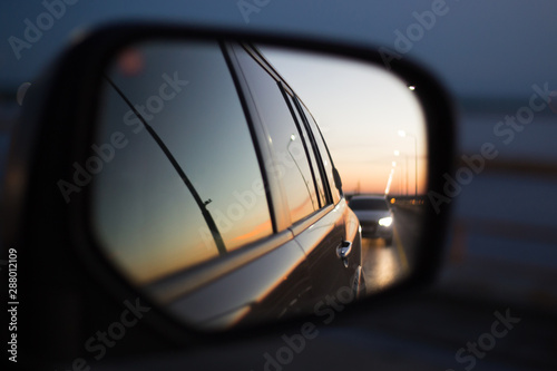 Fotografía  side mirror of a car in which a road with a traveling car is reflected at sunset