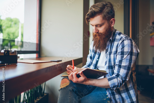Obraz Talented young bearded man in casual shirt drawing sketch in notebook enjoying leisure time in coffee shop.Skilled student writing down homework in notepad sitting in coworking.Copy space area - fototapety do salonu