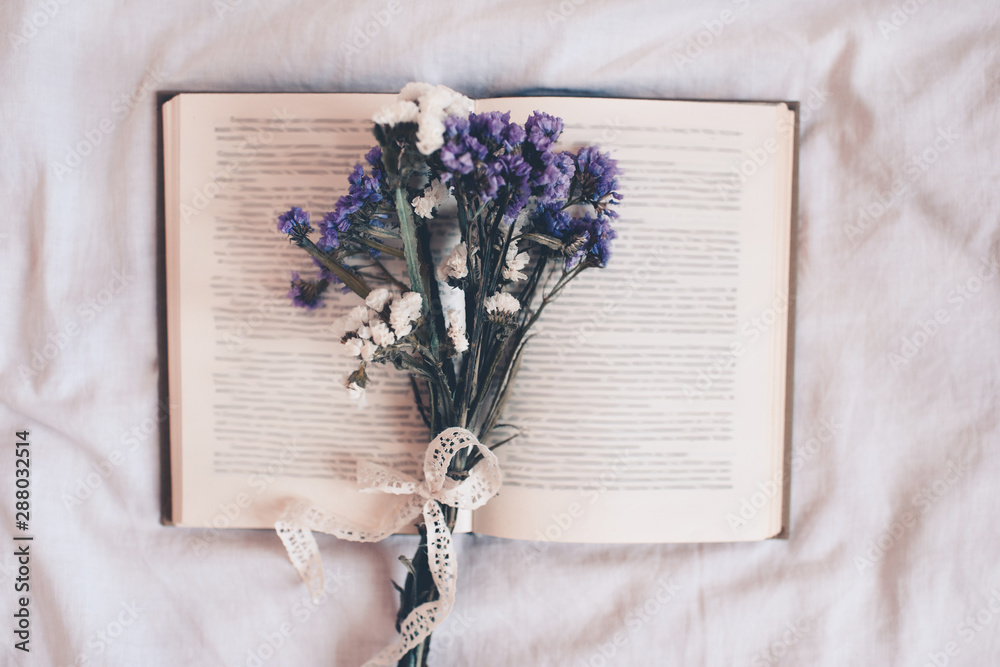 Fototapety, obrazy: Open book with dry flowers closeup over white. Top view. Autumn season.