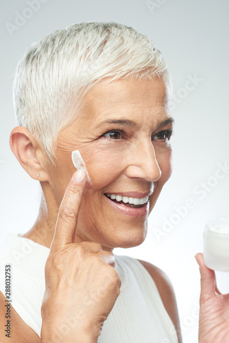 Gorgeous smiling Caucasian senior woman trying out new anti age cream. Beauty photography.