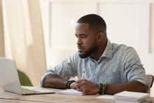 Concentrated Millennial African American Guy Focused On Online University Courses.