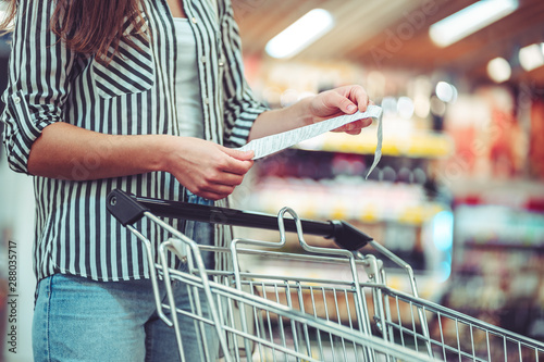 Fotografía  Woman with shopping cart in aisle checks and examines a sales receipt after purchasing food in a grocery store