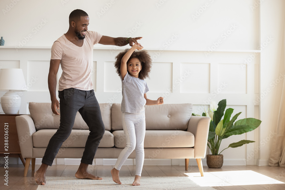 Fototapety, obrazy: Excited loving african american smiling father twisting cute little daughter.