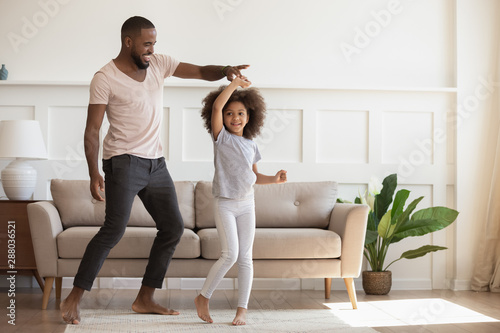 Photo Stands Coffee bar Excited loving african american smiling father twisting cute little daughter.