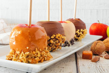 Variety Of Fall Candy Apples With Caramel, Chocolate And Nuts, Close Up On A Serving Plate Against A White Wood Background