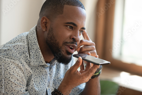 Photo Close up thoughtful african american guy using virtual assistant.