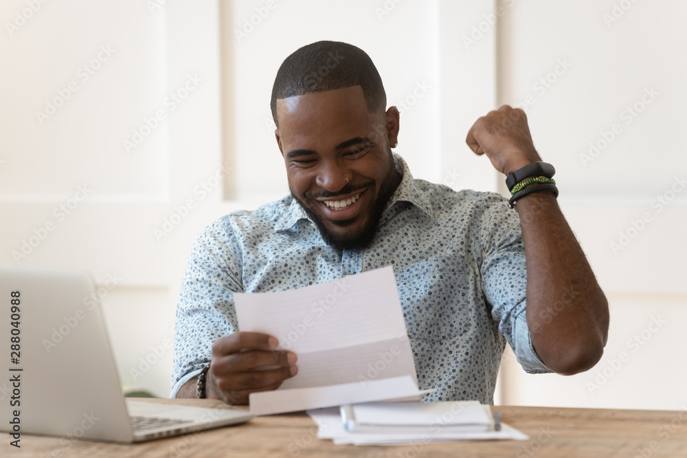 Fototapety, obrazy: Happy african american guy received banking loan approval.
