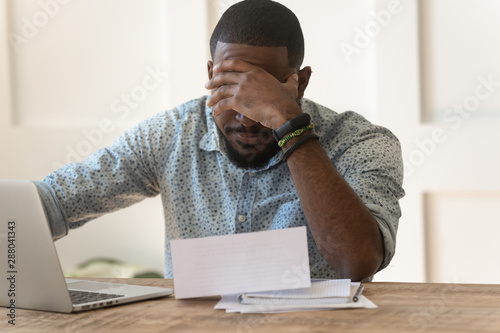 Stressed upset african american reading bad news in letter. Canvas