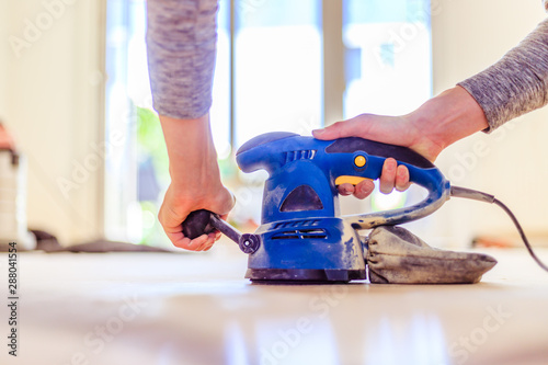 Obraz Renovating at home: sander tool for refreshing and grinding the wooden parquet floor - fototapety do salonu