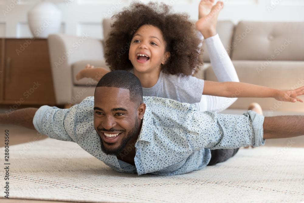 Fototapeta Happy black dad lying on floor with daughter on back.