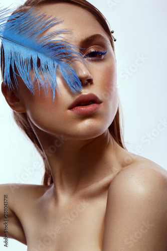 Beautiful tanned girl with creative make-up and blue eyelashes, feather in hand Canvas-taulu