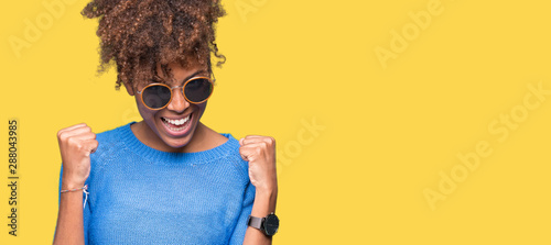 Poster Akt Beautiful young african american woman wearing sunglasses over isolated background very happy and excited doing winner gesture with arms raised, smiling and screaming for success. Celebration concept.