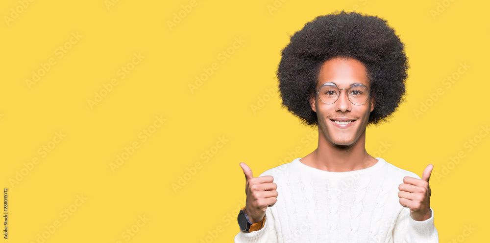 Fototapeta Young african american man with afro hair wearing glasses success sign doing positive gesture with hand, thumbs up smiling and happy. Looking at the camera with cheerful expression, winner gesture.