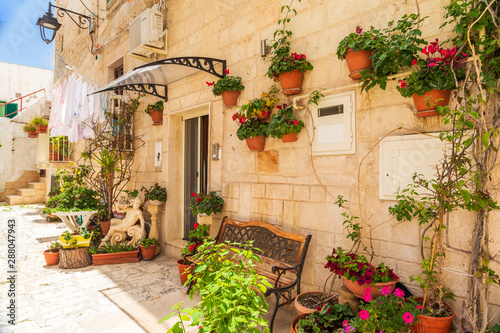 Fototapeten Schmale Gasse Italy, Apulia, Metropolitan City of Bari, Monopoli. Potted flowers on a stone building.