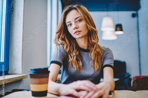 Fotomural Portrait of thoughtful hipster girl sitting at table with takeaway caffeine beve