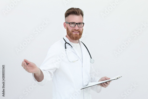 Valokuva friendly doctor with clipboard. isolated on white