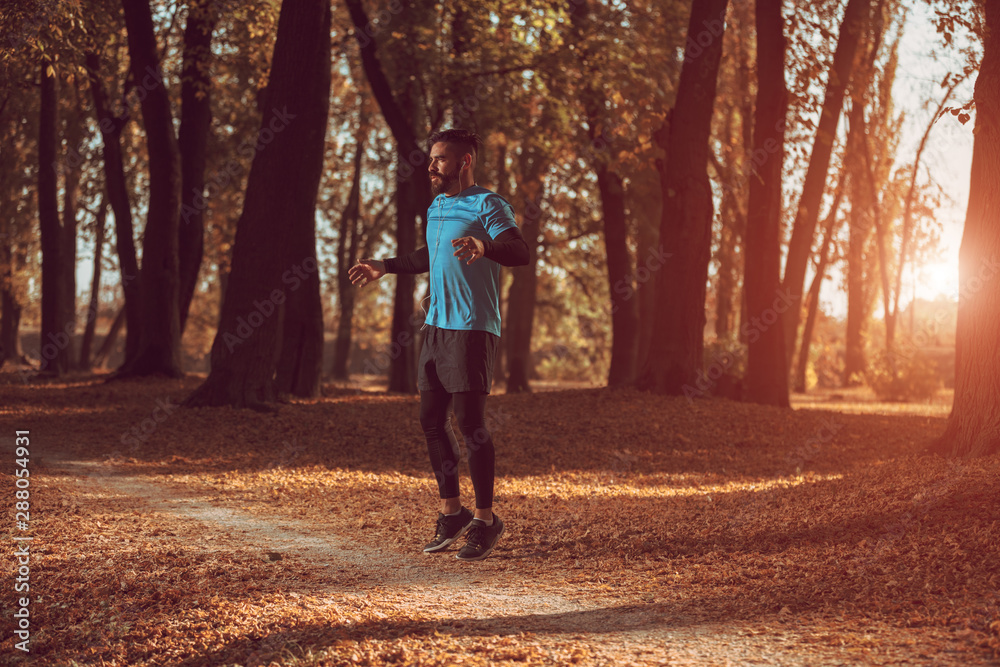 Fototapety, obrazy: A young, athletic man stretches in the park before a run