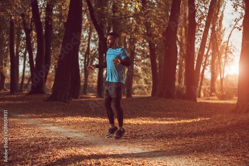 mata magnetyczna A young, athletic man stretches in the park before a run