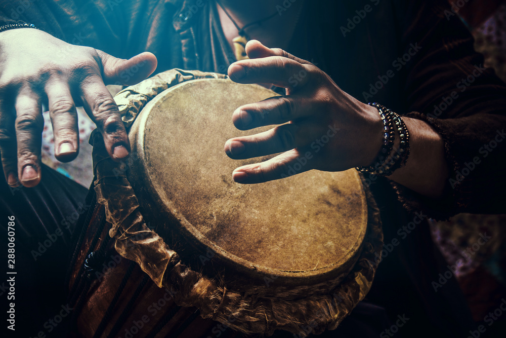 Fototapety, obrazy: A man playing an ethnic percussion musical instrument jembe. Drummer playing african musicembe