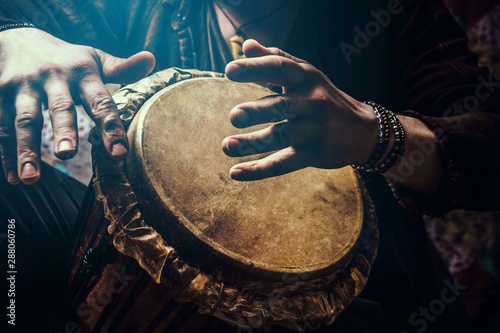 A man playing an ethnic percussion musical instrument jembe. Drummer playing african musicembe - 288060786