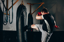 Muscular Kickbox Fighter Exercising With Punch Bag At The Gym