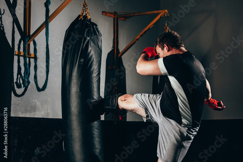 Photo Muscular kickbox fighter exercising with punch bag at the gym