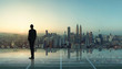 Businessman standing at transparent glass floor on rooftop with city skyline, success and thinking concept .