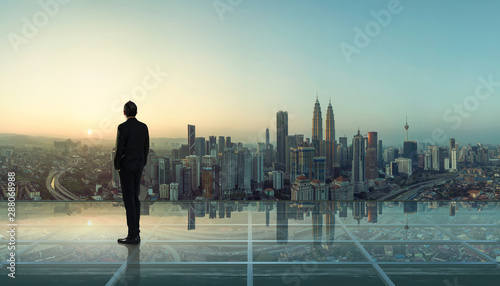 Fotomural  Businessman standing at transparent glass floor on rooftop with city skyline, success and thinking concept