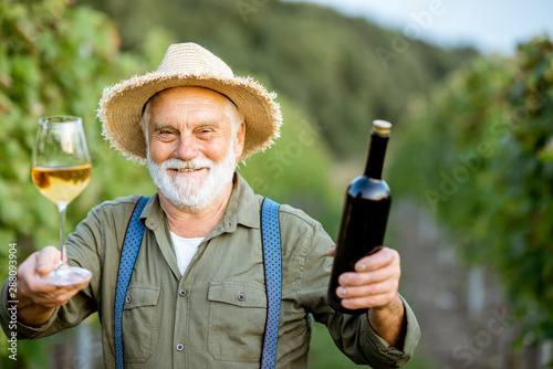 Fotografía Portrait of a happy senior well-dressed winemaker checking wine quality, standin