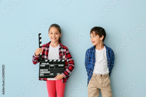Fényképezés Cute little children with movie clapper on color background