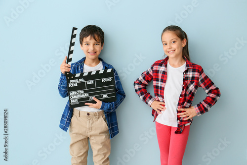 Cute little children with movie clapper on color background Wallpaper Mural