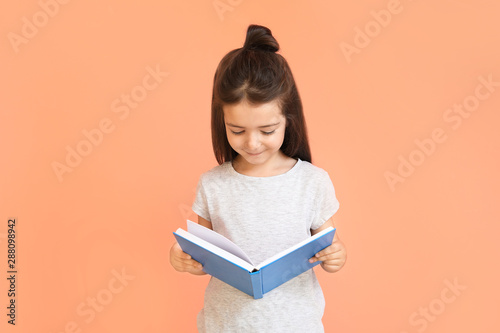Fotomural  Cute little girl with book on color background