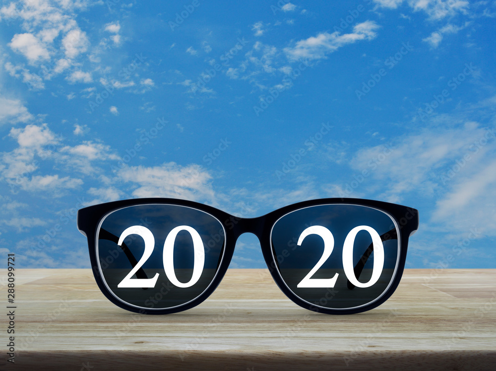 Fototapeta 2020 white text with black eye glasses on wooden table over blue sky with white clouds, Business vision happy new year 2019 concept