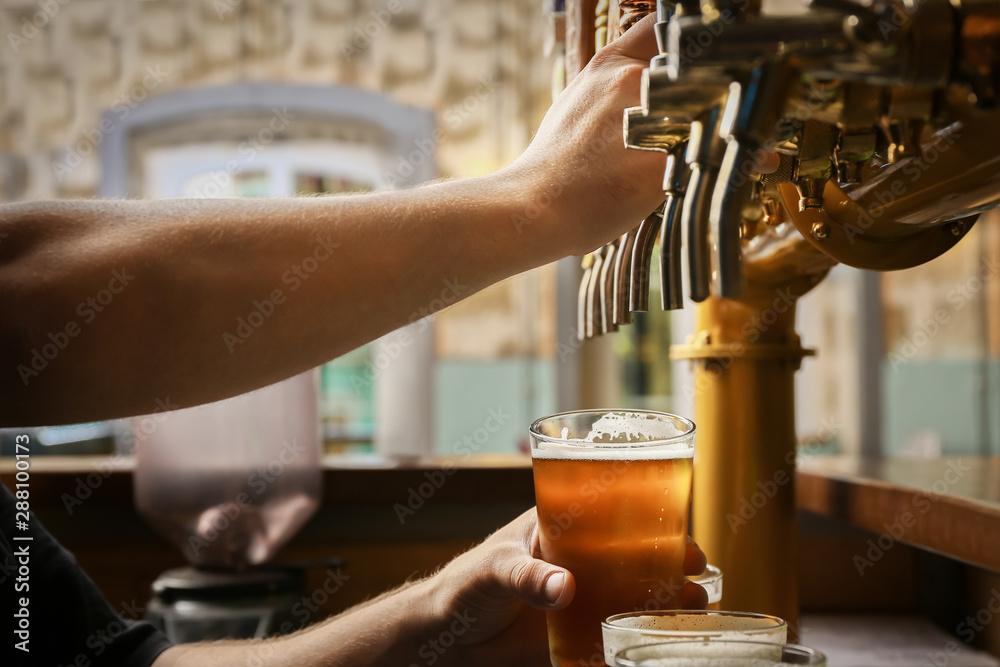Fototapeta Barman pouring fresh beer in glass, closeup