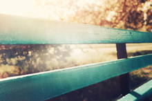 Wooden Blue Bench In City Park. With Sun Rays And Bokeh. Selective Focus