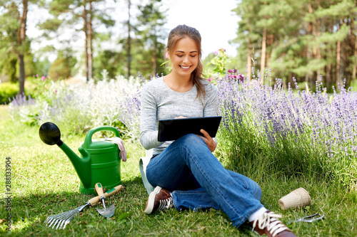 Tablou Canvas gardening, technology and people concept - happy young woman or gardener with ta