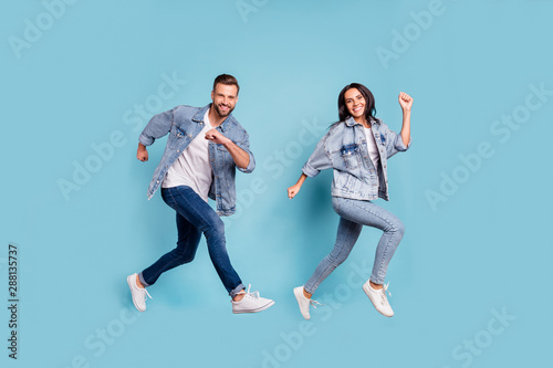 Obraz Full length body size photo of rejoicing couple of friends running towards shopping mall for sales while isolated with blue background - fototapety do salonu