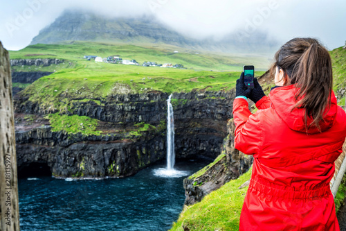 Foto auf AluDibond Olivgrun Young female travelers is taking photo of Mulafossur Waterfall with the village Gasadalur in background, Faroe Islands.