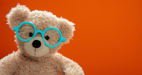 Cute teddy wearing eyeglasses against orange color background